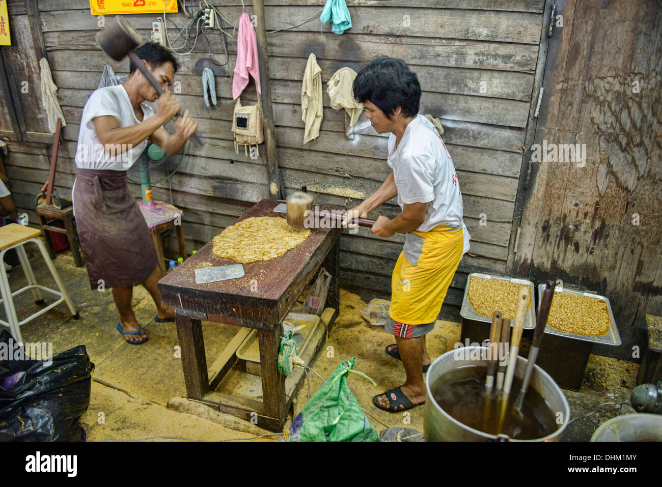 workers pounding peanut brittle at the Vegetarian Festival in Bangkok, Thailand - Stock Image