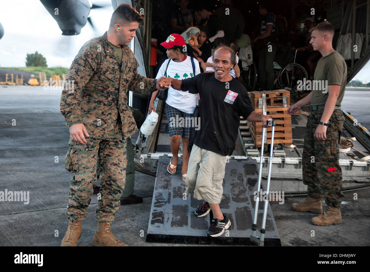 US Marines help offload Filipino civilians out of a U.S. Marine C-130 Hercules aircraft at Villamor Air Base evacuated from Tacloban November 12, 2013 in Manila, Philippines. The super typhoon devastated wide areas of the islands and killed as many as 10,000 people. - Stock Image