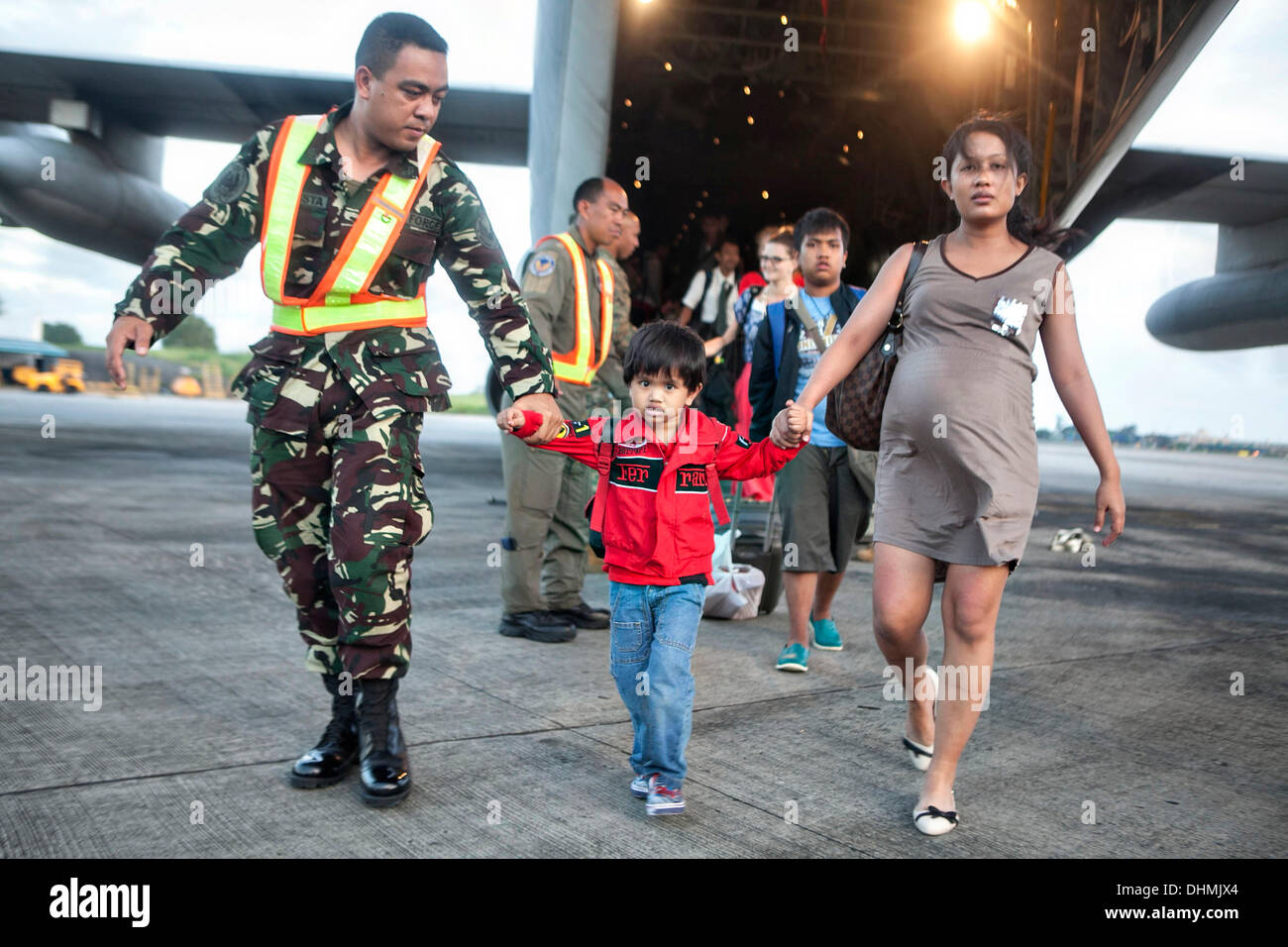 An Airman with the Philippine Air Force helps offload Filipino civilians out of a U.S. Marine C-130 Hercules aircraft at Villamor Air Base evacuated from Tacloban November 12, 2013 in Manila, Philippines. The super typhoon devastated wide areas of the islands and killed as many as 10,000 people. - Stock Image