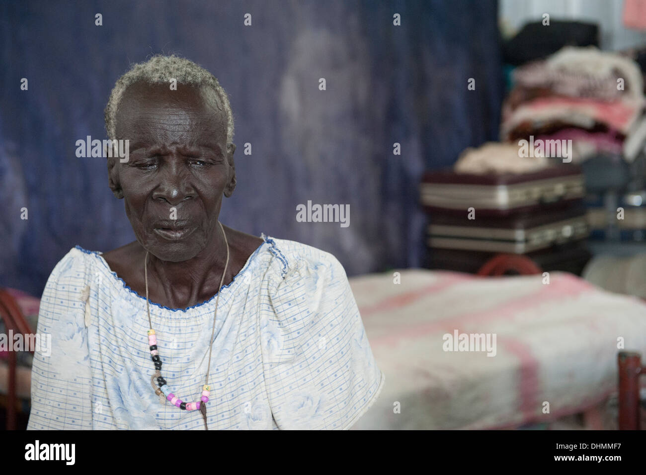 An elderly woman awaits further transport to her original home area near Malakal in South Sudan. - Stock Image