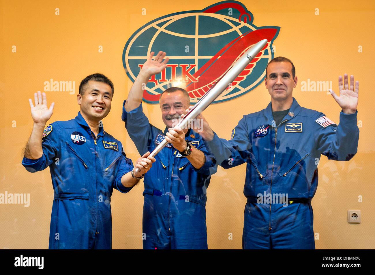 International Space Station Expedition 38 Flight Engineer Koichi Wakata of the Japan Aerospace Exploration Agency, left, Soyuz Commander Mikhail Tyurin of Roscosmos, and, Flight Engineer Rick Mastracchio of NASA, right, smile as they hold an Olympic torch that will be flown with them to the International Space Station during a press conference prior to launch November 6, 2013 at the Baikonur Cosmodrome, Kazakhstan. Tyurin, Mastracchio, and, Wakata will spend the next six months aboard the International Space Station. - Stock Image