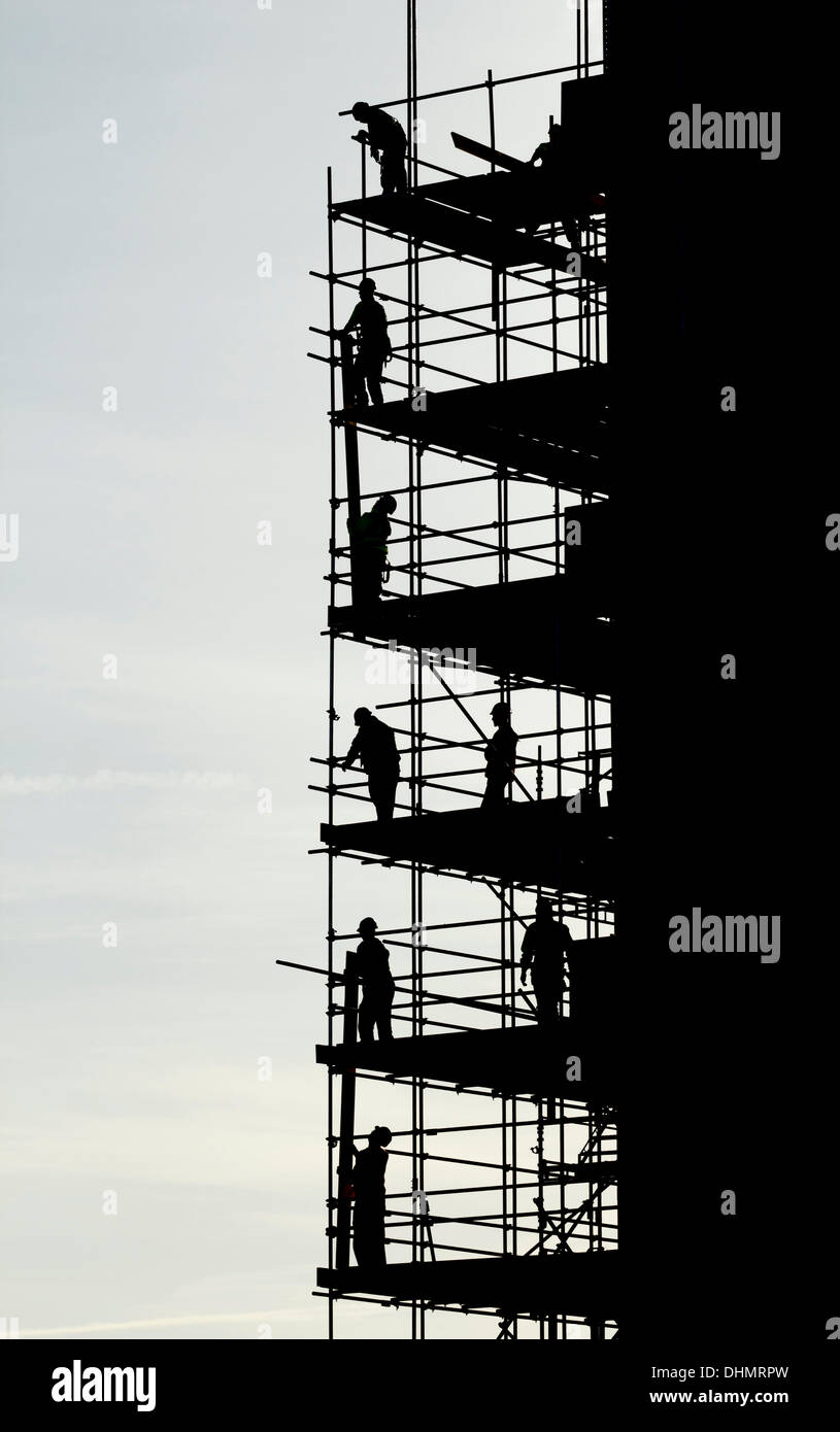 .  Scaffolders working on block of flats silhouetted againt bright Autumnal sky - Stock Image