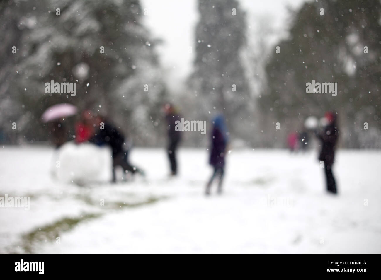 out of focus people playing in the snow making a snowman having snowball fight in parkland setting - Stock Image