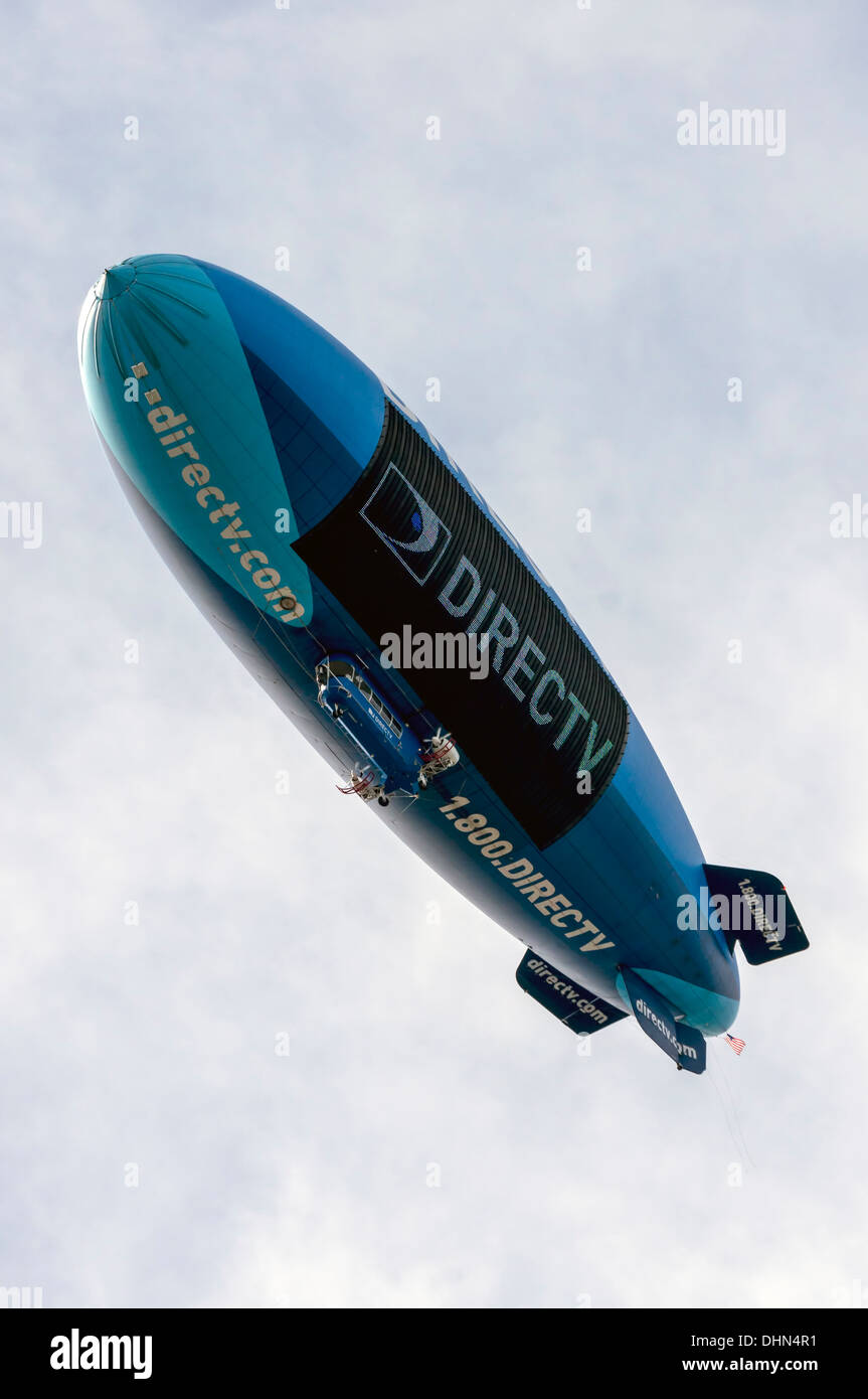 Blue and turquoise hot air blimp navigates above the football stadium advertising DirecTV in Gainesville, Florida, USA. - Stock Image
