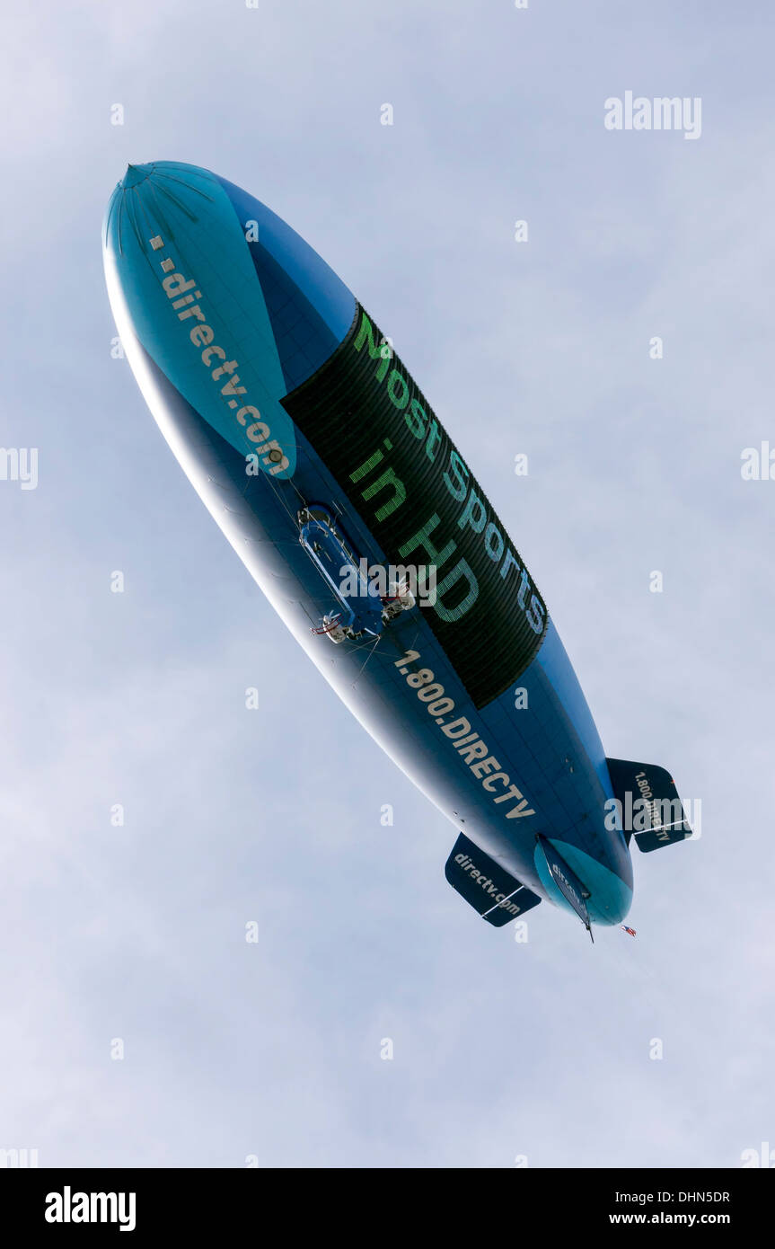 Blue and turquoise blimp navigates above football stadium advertising DirecTV Most Sports in HD, Gainesville, Florida, USA. - Stock Image