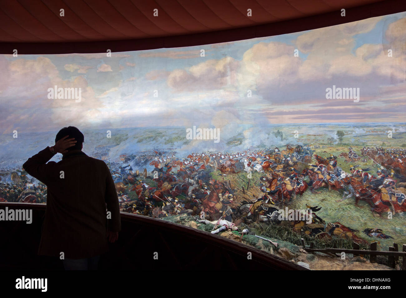Tourist watching battlefield scenes at Panorama, museum showing a 360° fresco of Battle of Waterloo at Braine-l'Alleud, Belgium - Stock Image