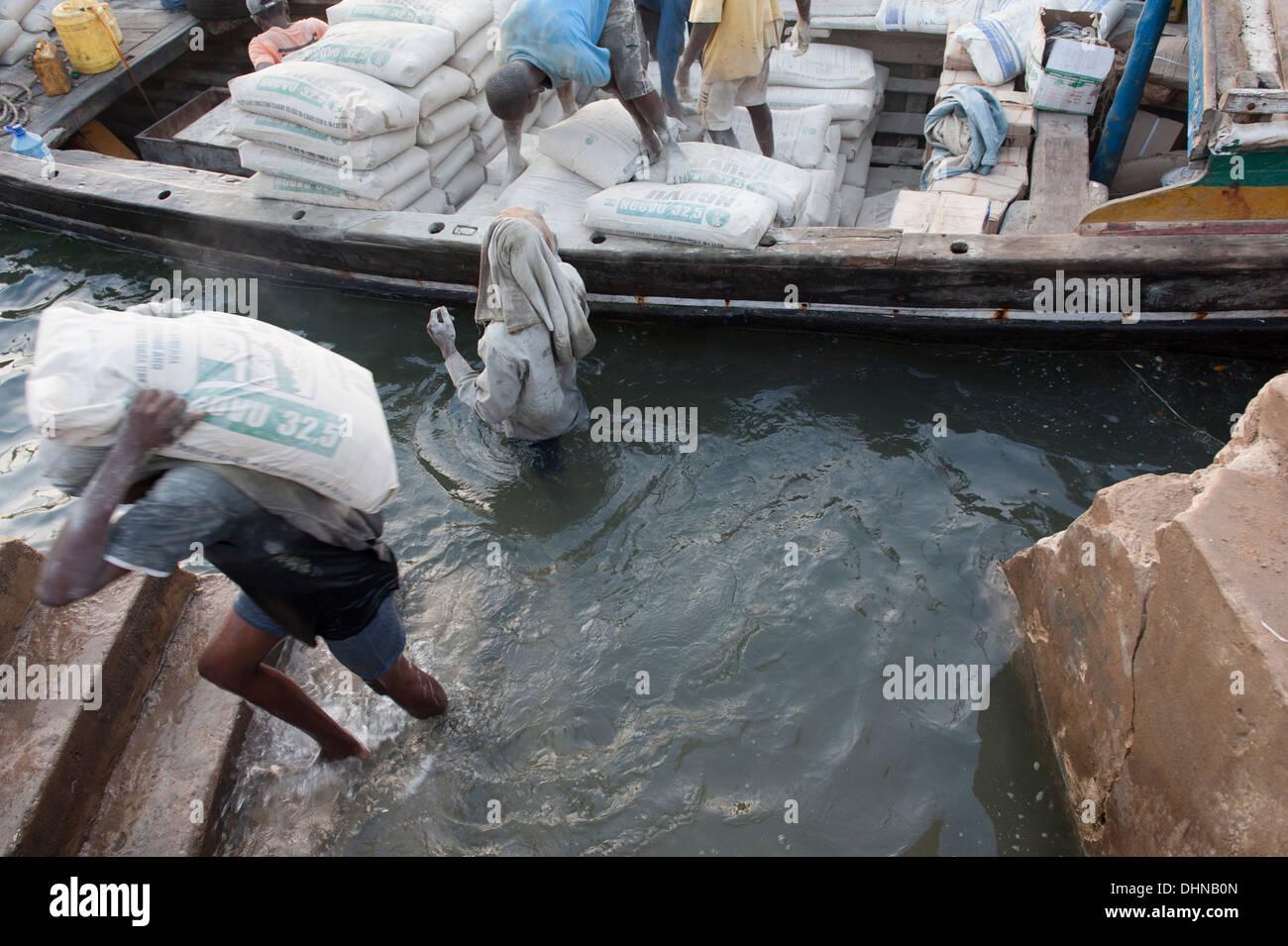 Men unload a boat in Lamu town, Kenya - Stock Image
