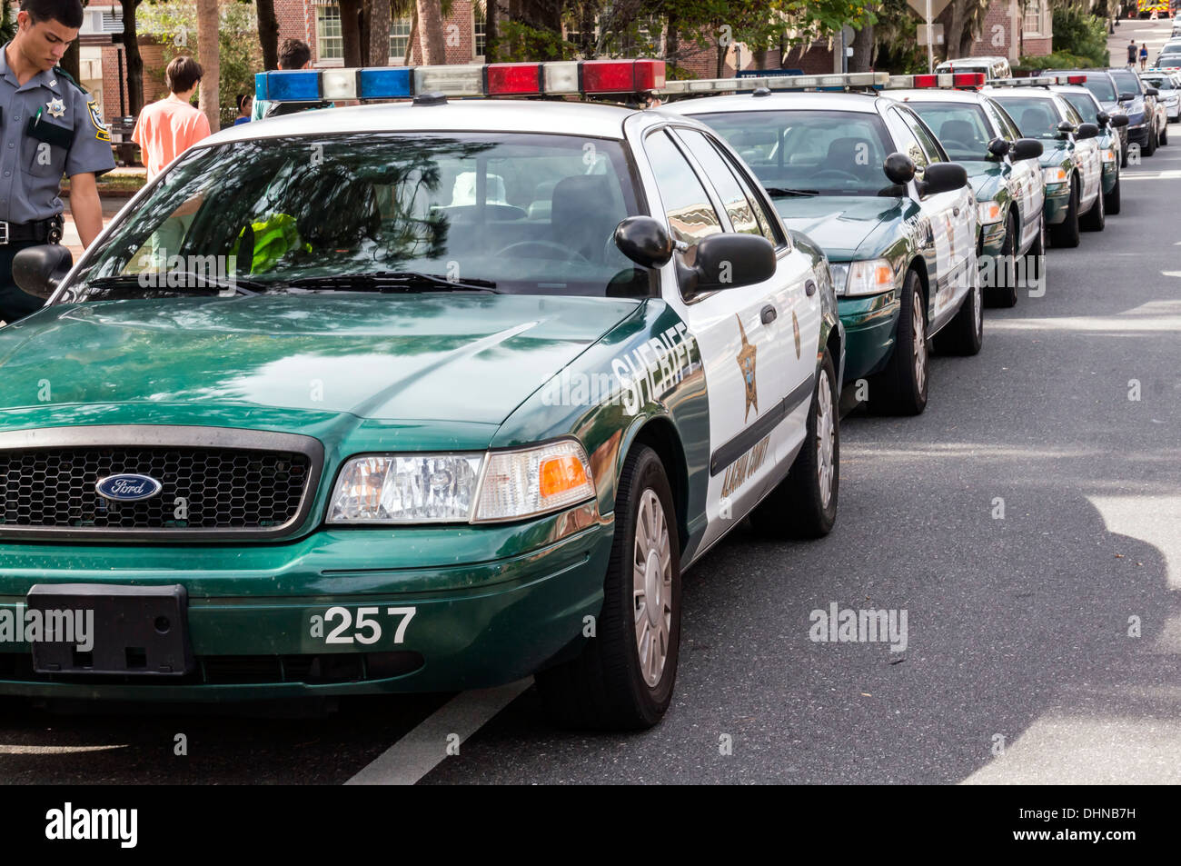 Line of police cars or cruisers parallel parked in front of the stadium on the University of Florida campus in Gainesville, Flor - Stock Image