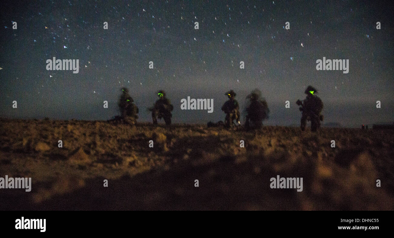 A US Army soldier wearing night vision goggles keeps watch during a nighttime search operation October 14, 2013 in Helmand province, Afghanistan, Oct. 14, 2013. Afghan and coalition forces arrested a Taliban improvised explosive device cell leader during the operation. - Stock Image
