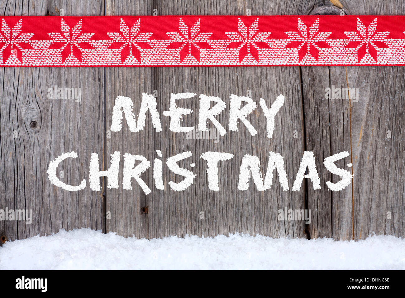 Christmas greetings with snow script on old wooden board with a christmas greetings with snow script on old wooden board with a red white fabric ribbon m4hsunfo