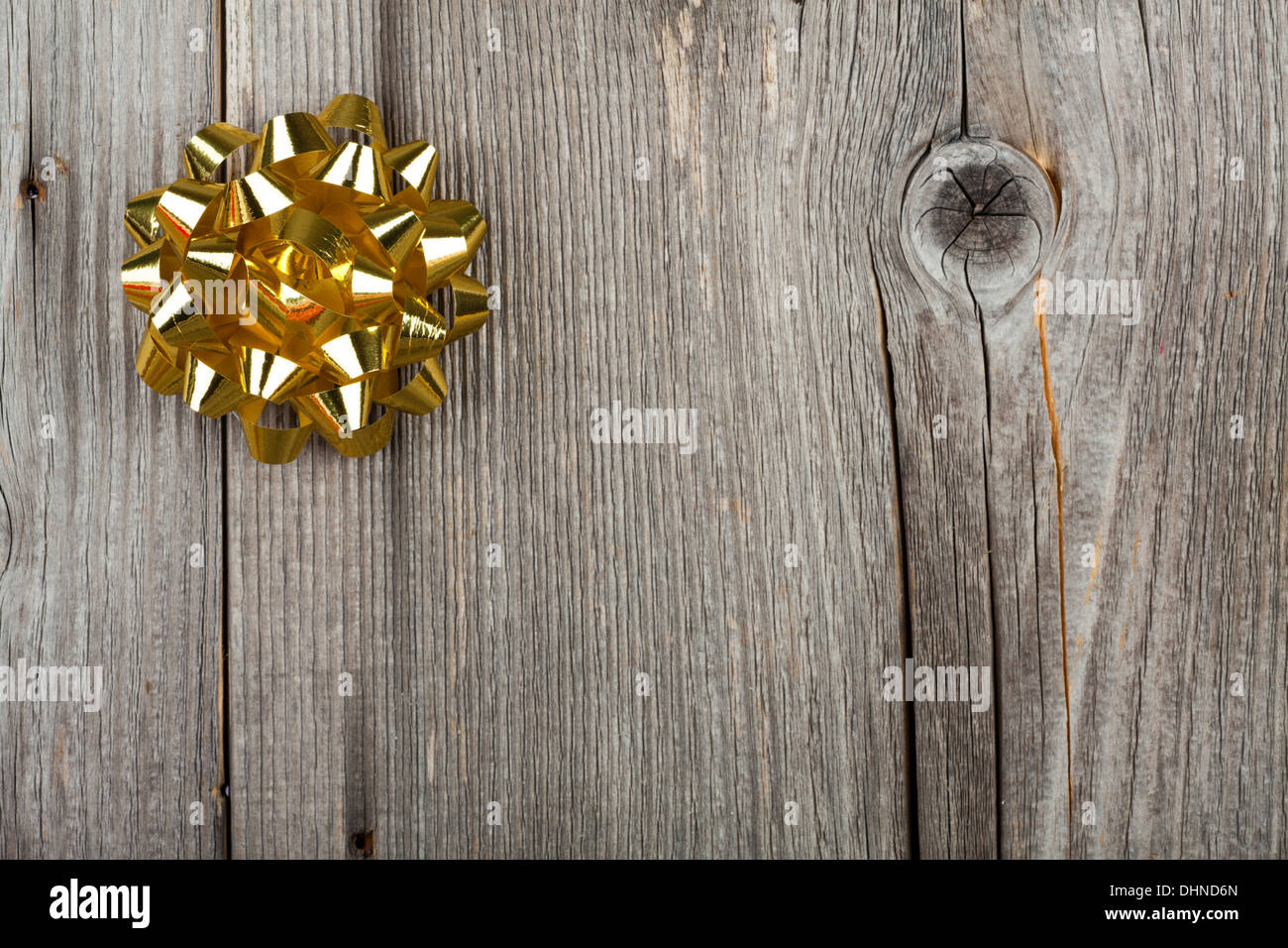 Christmas Greeting Card with a golden Ribbon Bow on old wooden Board - Stock Image