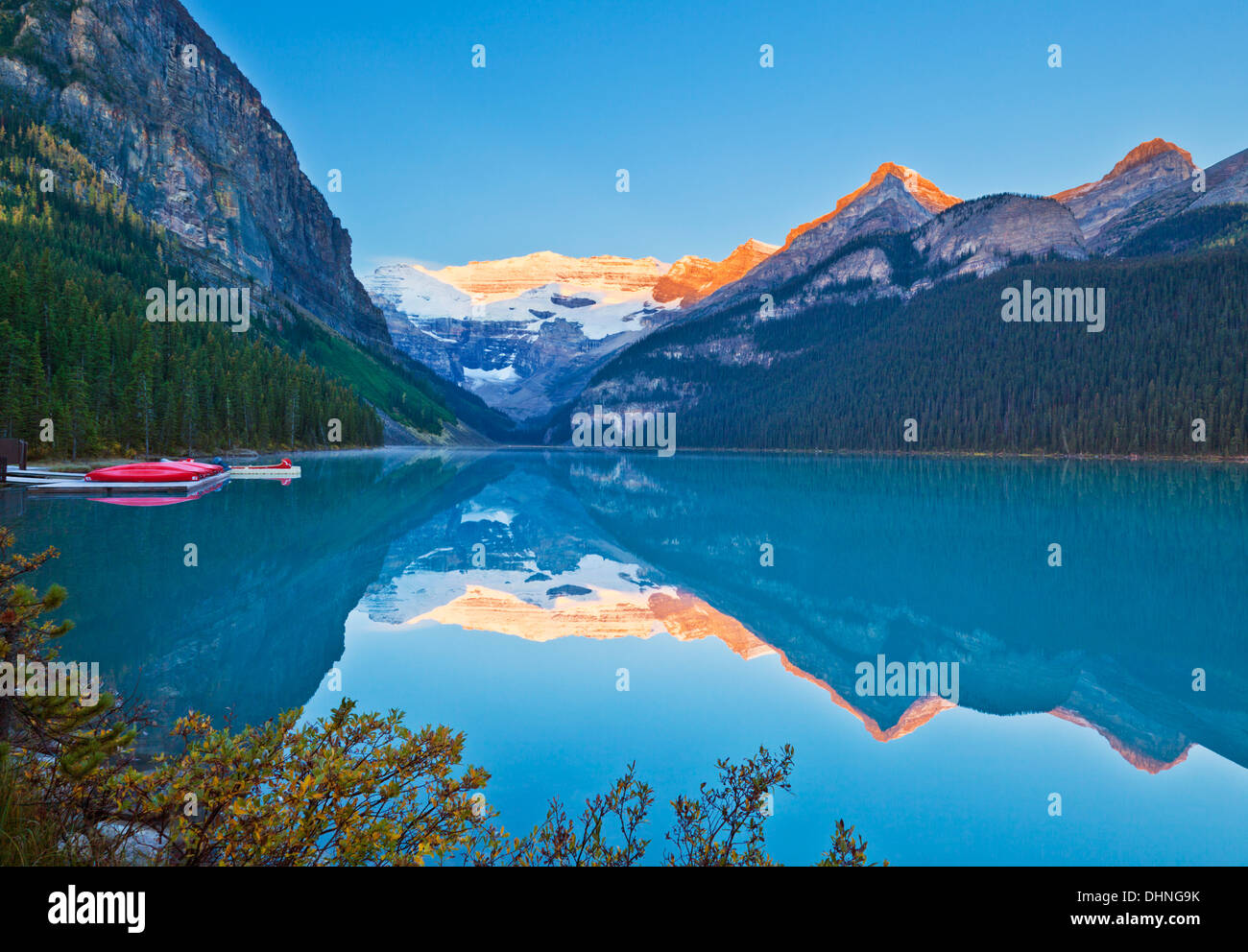 Red canoes for hire on Lake Louise Banff national Park Alberta Canadian Rockies Canada - Stock Image