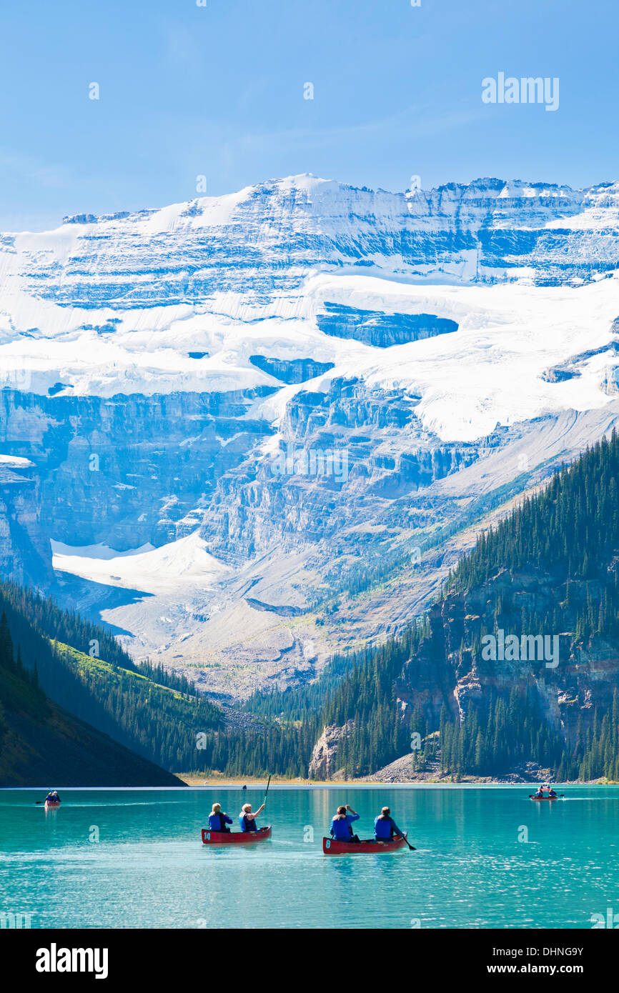 Tourists in Red canoes for hire on Lake Louise Banff national Park Alberta Canadian Rockies Canada - Stock Image