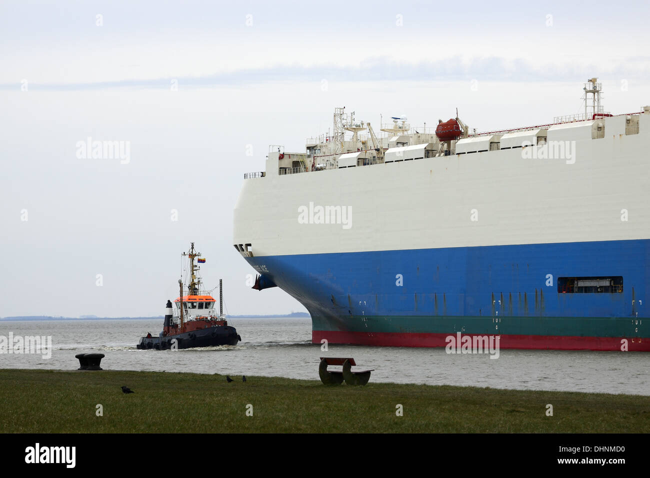 Tugs and overseas ferry - Stock Image