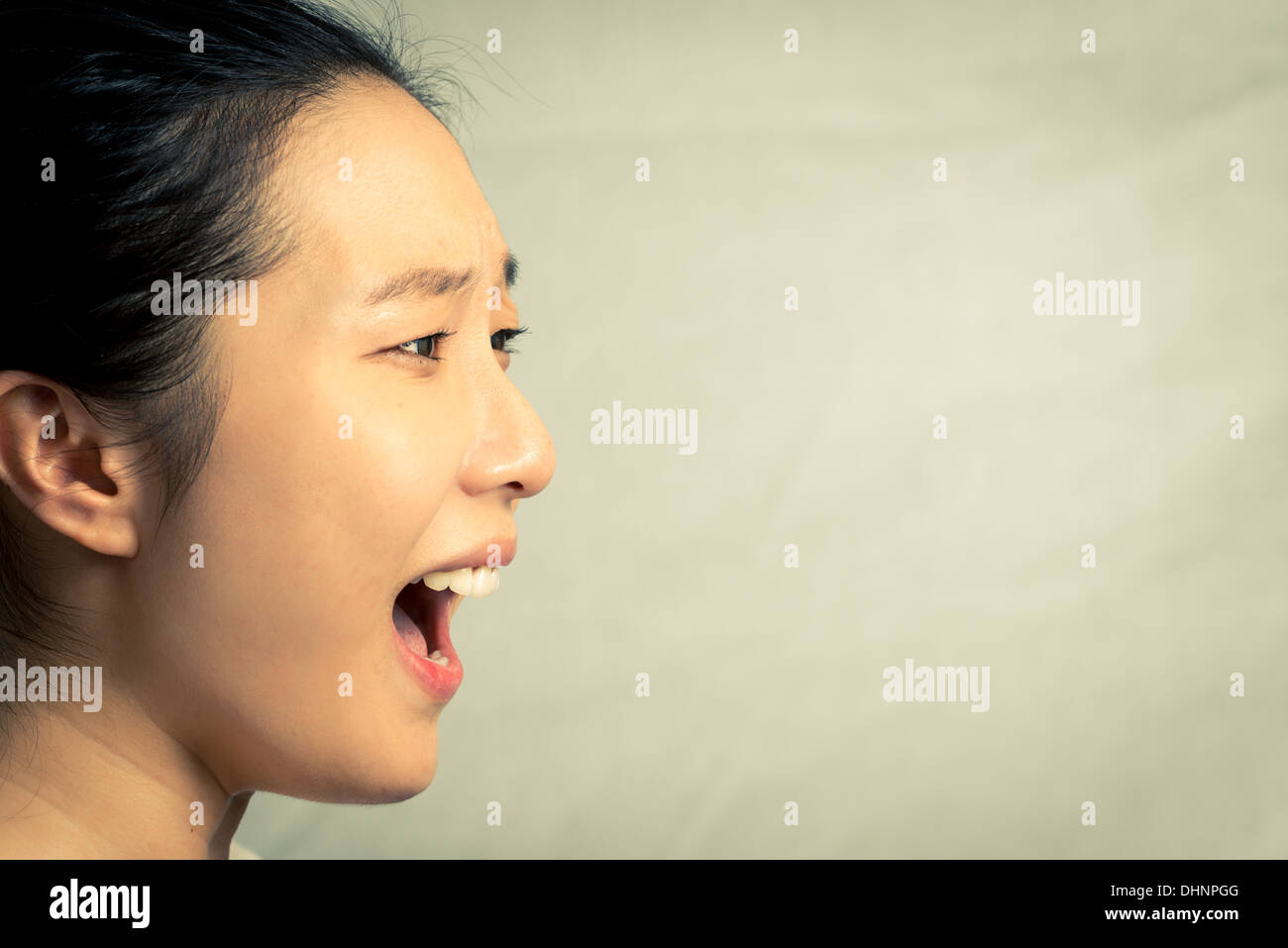 Young woman shouting, with fashion tone and background - Stock Image