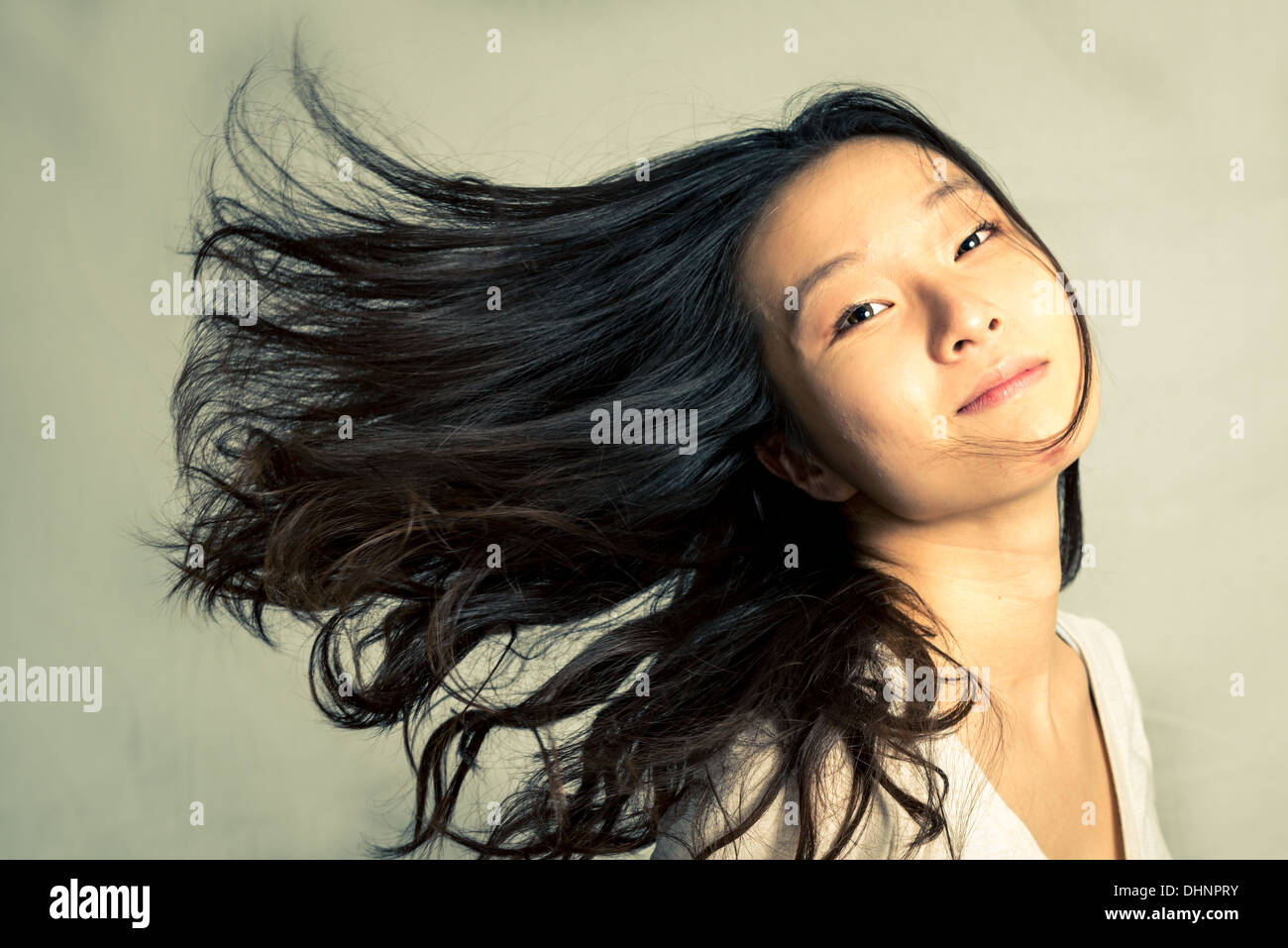 Young woman flicking her hair and posing, with fashion tone and background - Stock Image