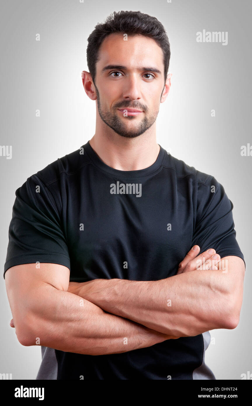 Personal trainer with is arms crossed, in a grey background - Stock Image