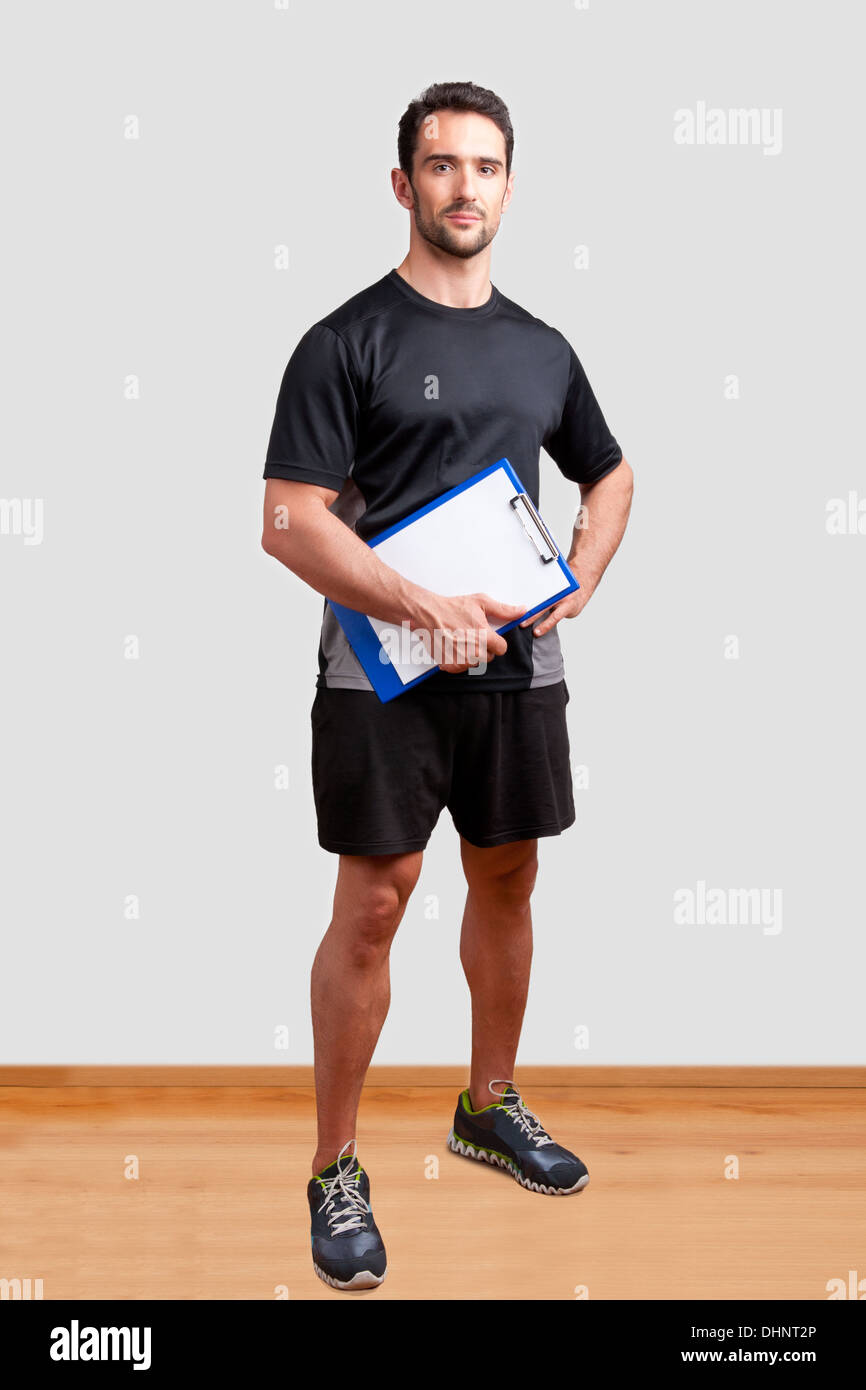 Personal Trainer, with a pad in his hand, in a gym Stock Photo