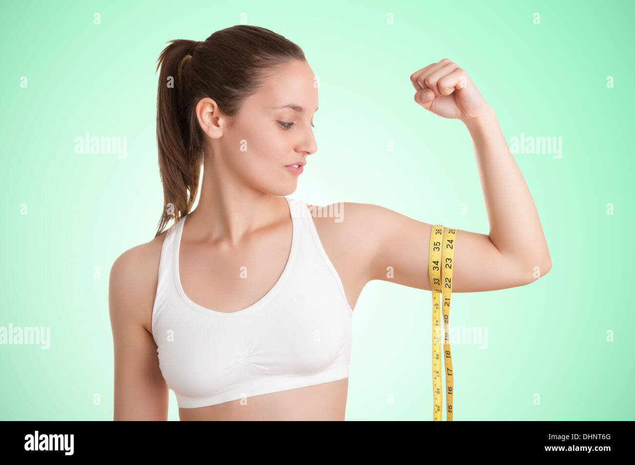 Powerful woman measuring her biceps with a yellow measuring tape in a green background - Stock Image