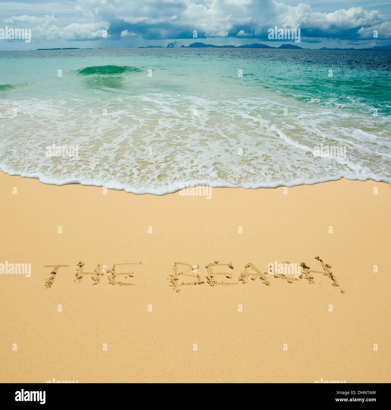 the beach written in a sandy tropical beach - Stock Image
