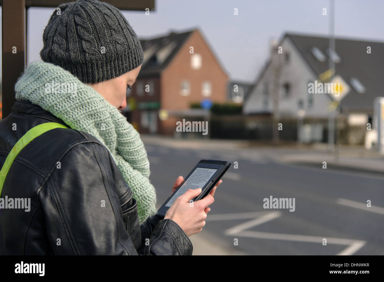 young woman with ebook on the roadside - Stock Image