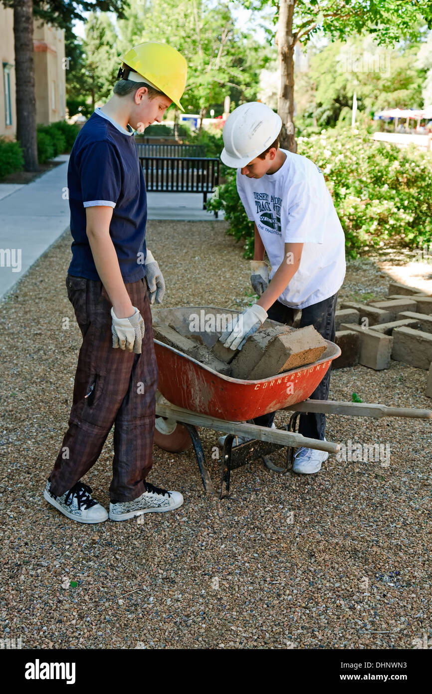 Student volunteers load wheel barrow with adobe bricks, San Miguel Church restoration project, Santa Fe, New Mexico USA - Stock Image