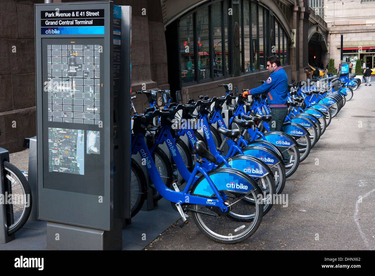 A man checks out a bike from a Citi Bike NYC bike sharing program docking station in Pershing Square in New York City. - Stock Image