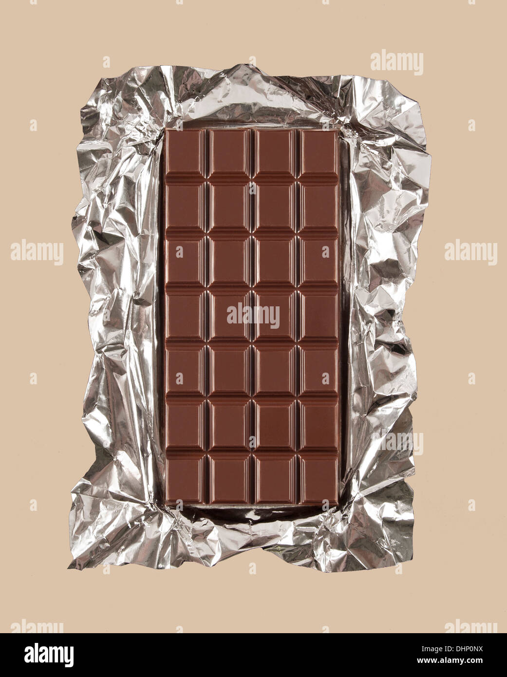 Chocolate candy bar with foil wrapper unwrapped - Stock Image