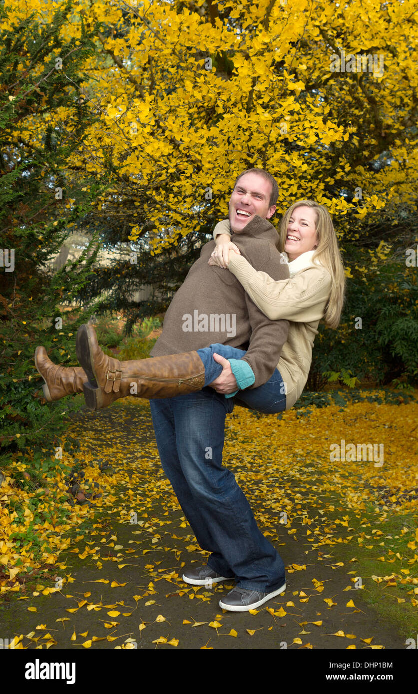 Vertical photo of happy adult couple with husband giving his wife a piggy back ride in the park during a nice day in the autumn - Stock Image