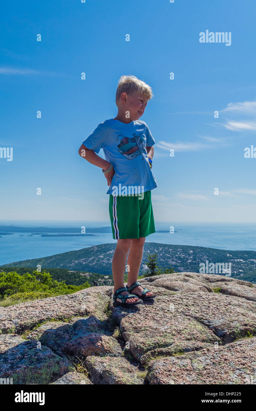 A blond haired boy stands on a large rock formation with his hands on his hips, on Cadillac Mountain in Acadia National Park, ME - Stock Image