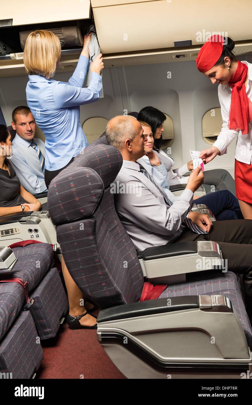 Flight attendant check passenger tickets in plane cabin - Stock Image
