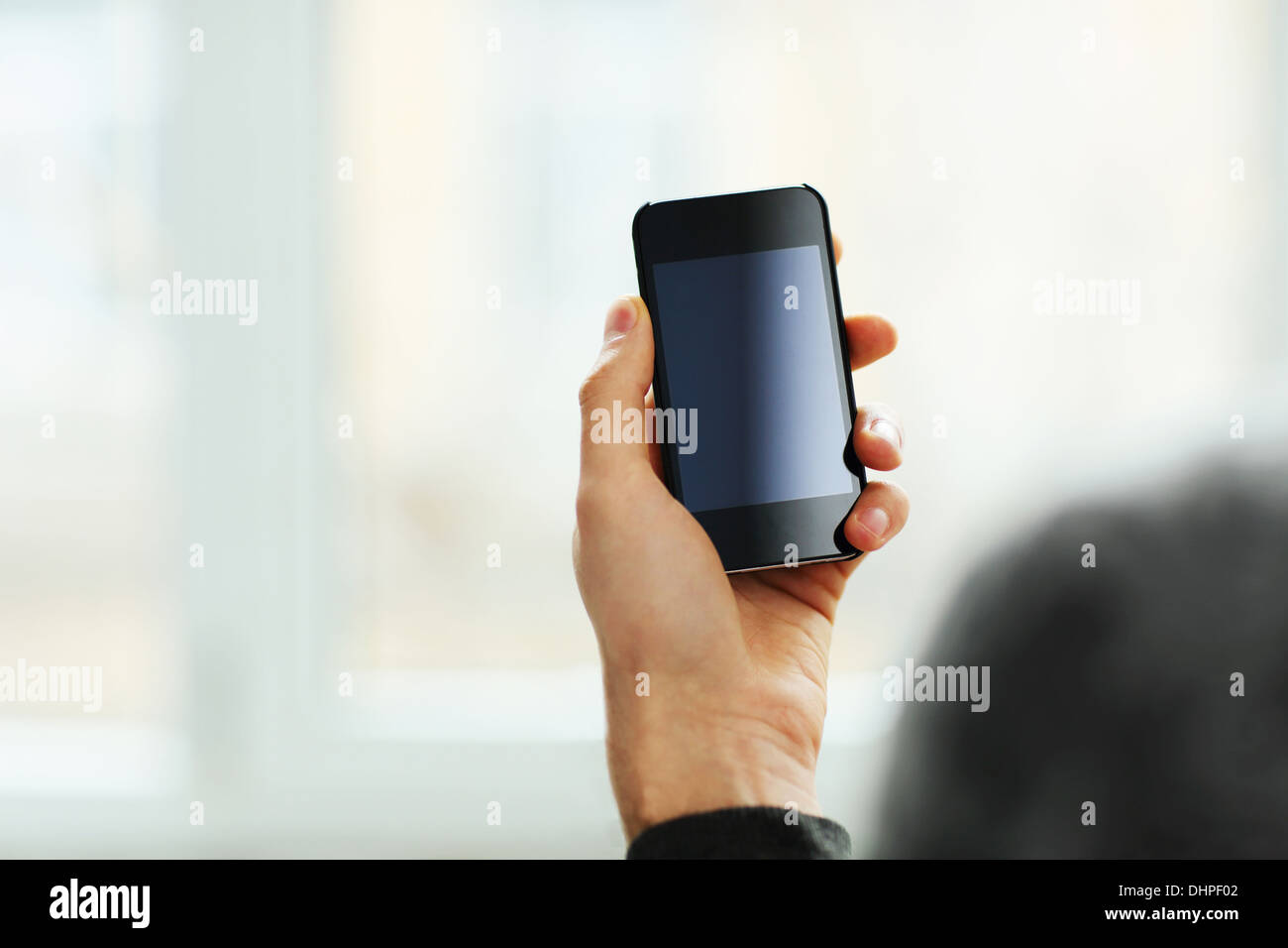 Closeup image of a male hand showing smartphone display - Stock Image
