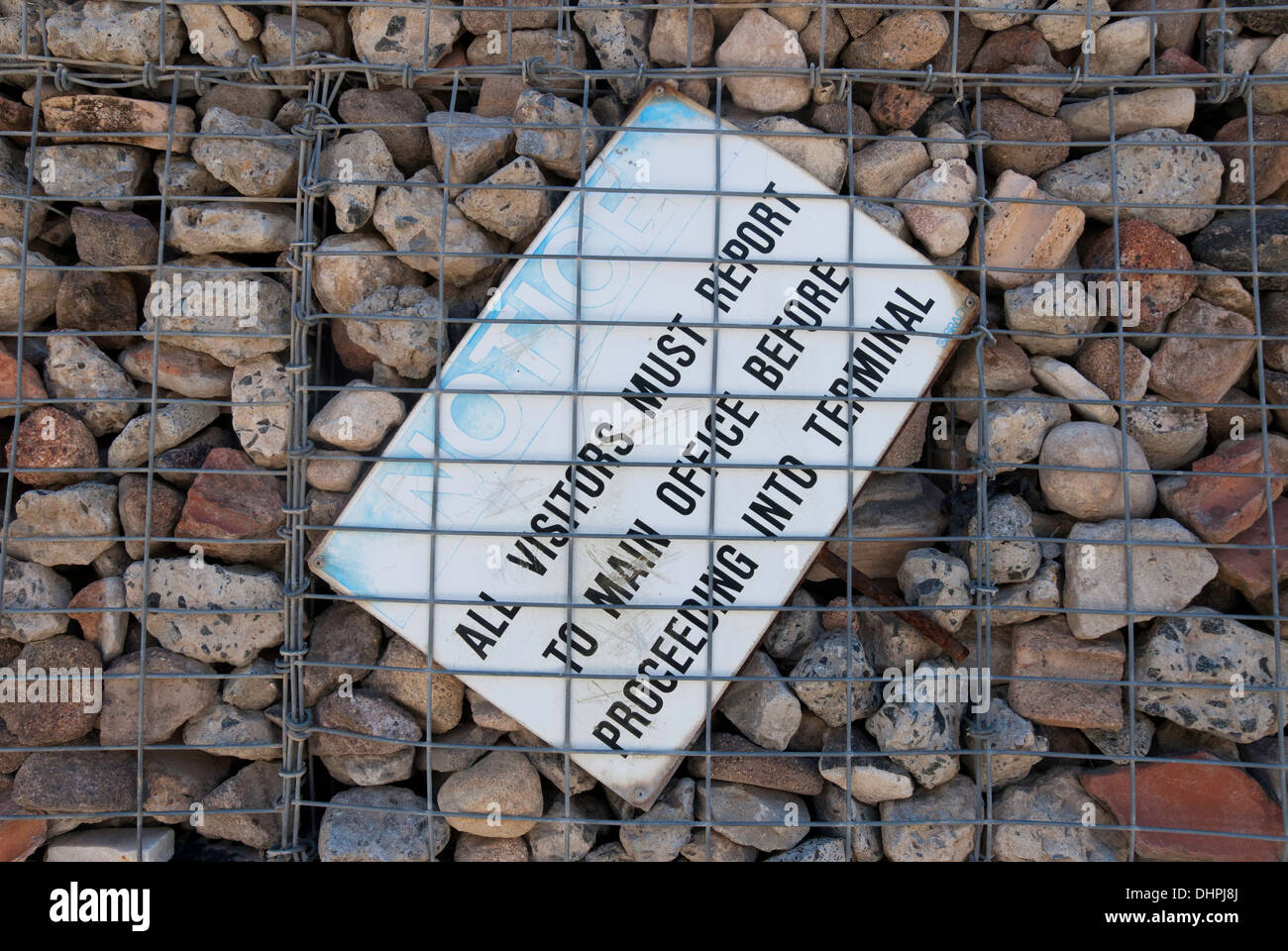 Industrial sign wedged into rubble wall in a Sydney park, Australia - Stock Image