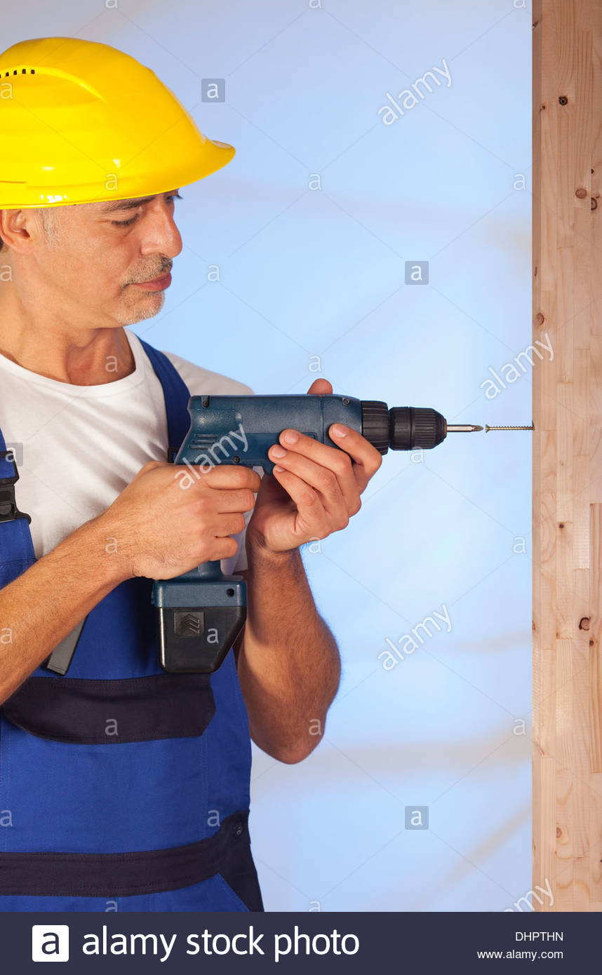 Construction worker using cordless screwdriver DIY - Stock Image