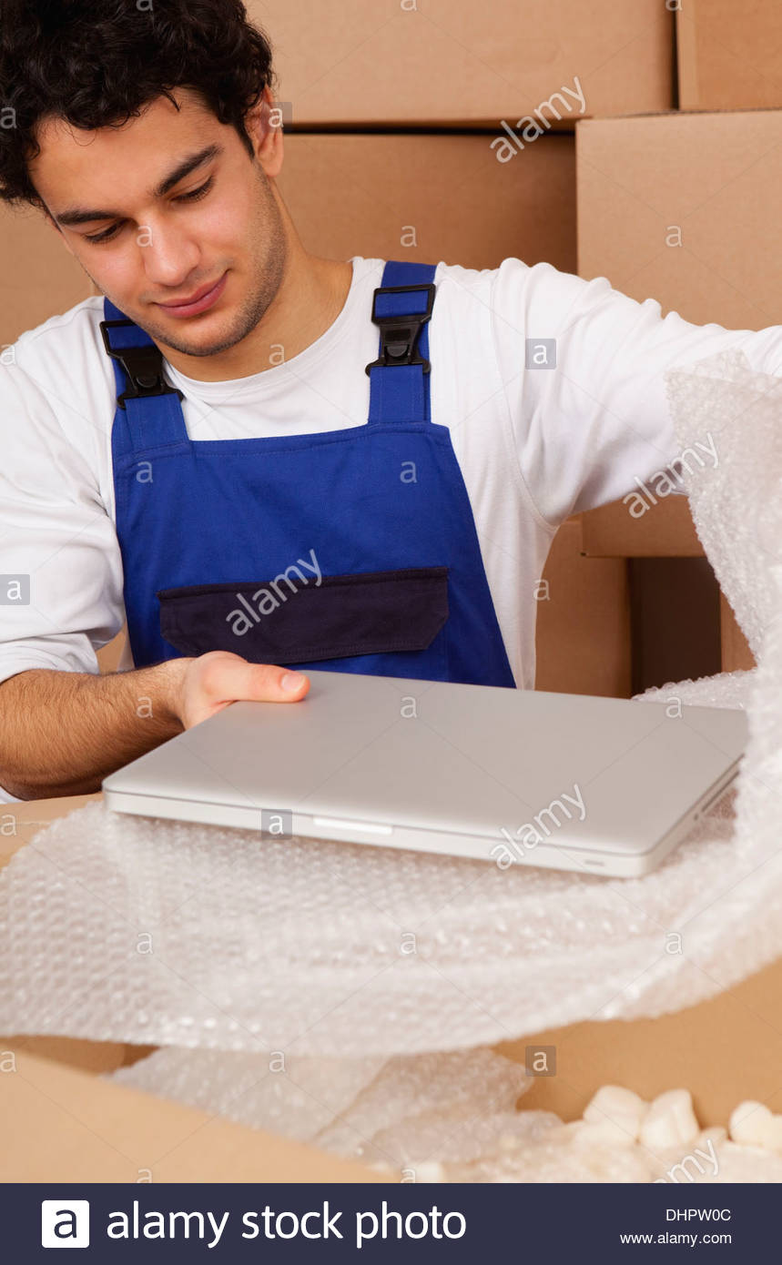 man young new home unpacking moving in boxes - Stock Image