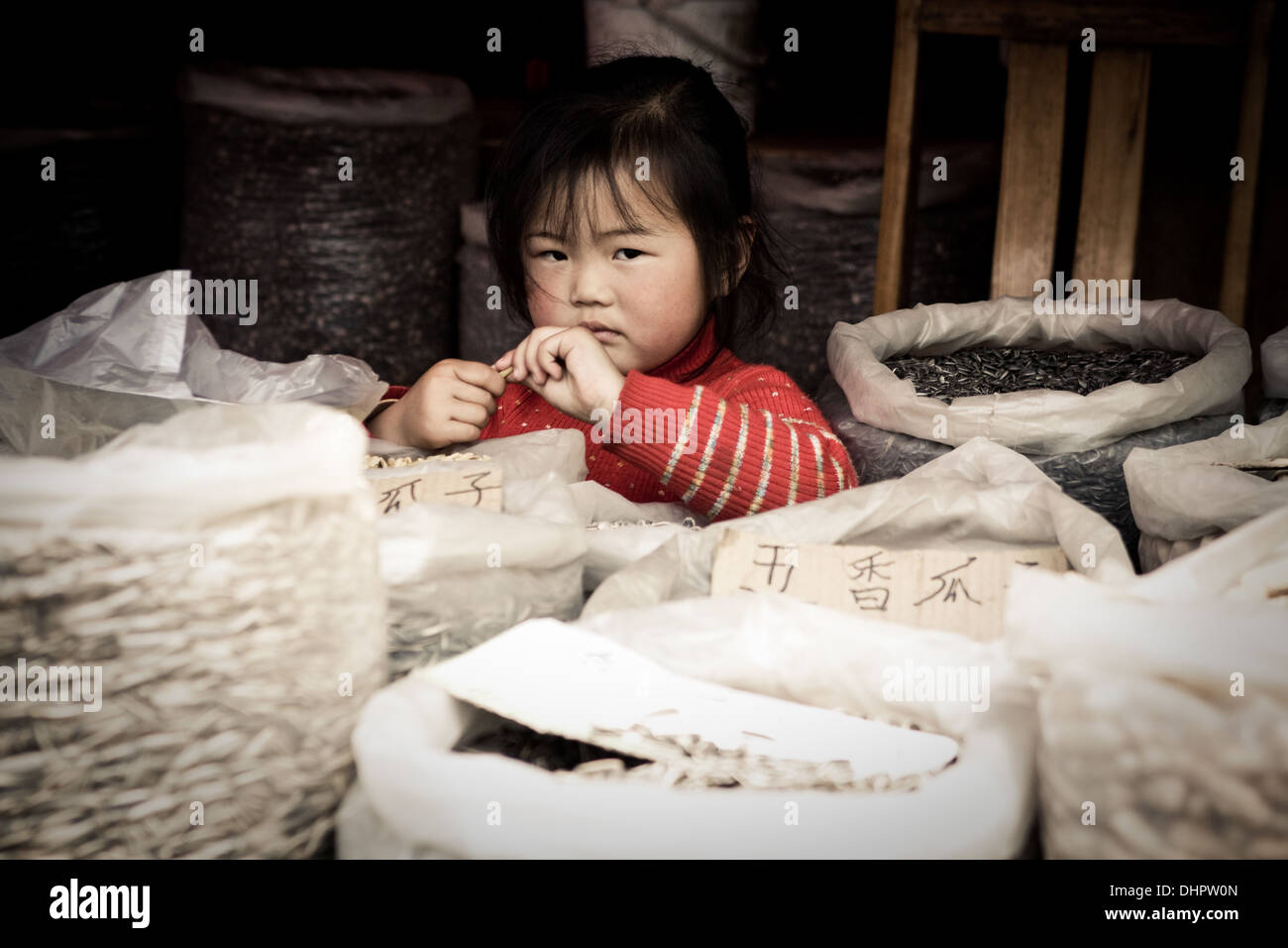 Young chinese child worker in Shanghai China. Selling on the streets of the market as a underage worker. - Stock Image