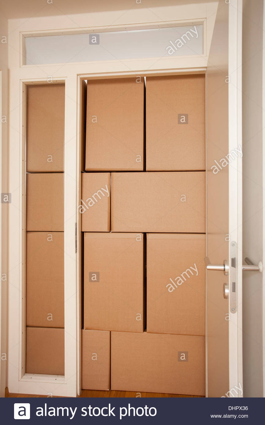 Cardboard boxes moving in door frame new home full - Stock Image