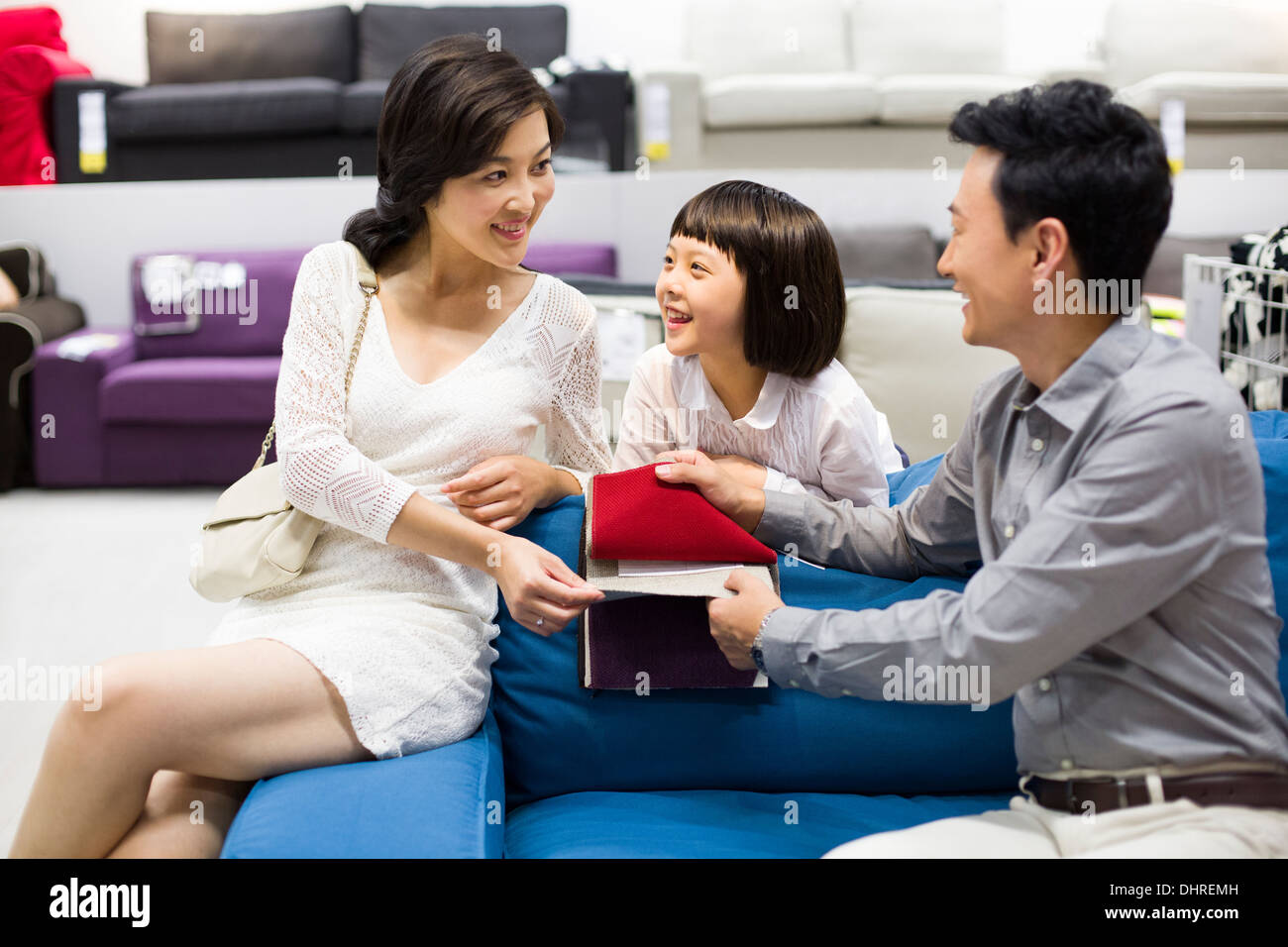 Happy Family Shopping For Sofa In Furniture Shop Stock Photo