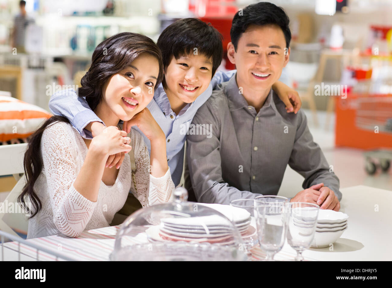 Cheerful family sitting side by side and smiling Stock Photo