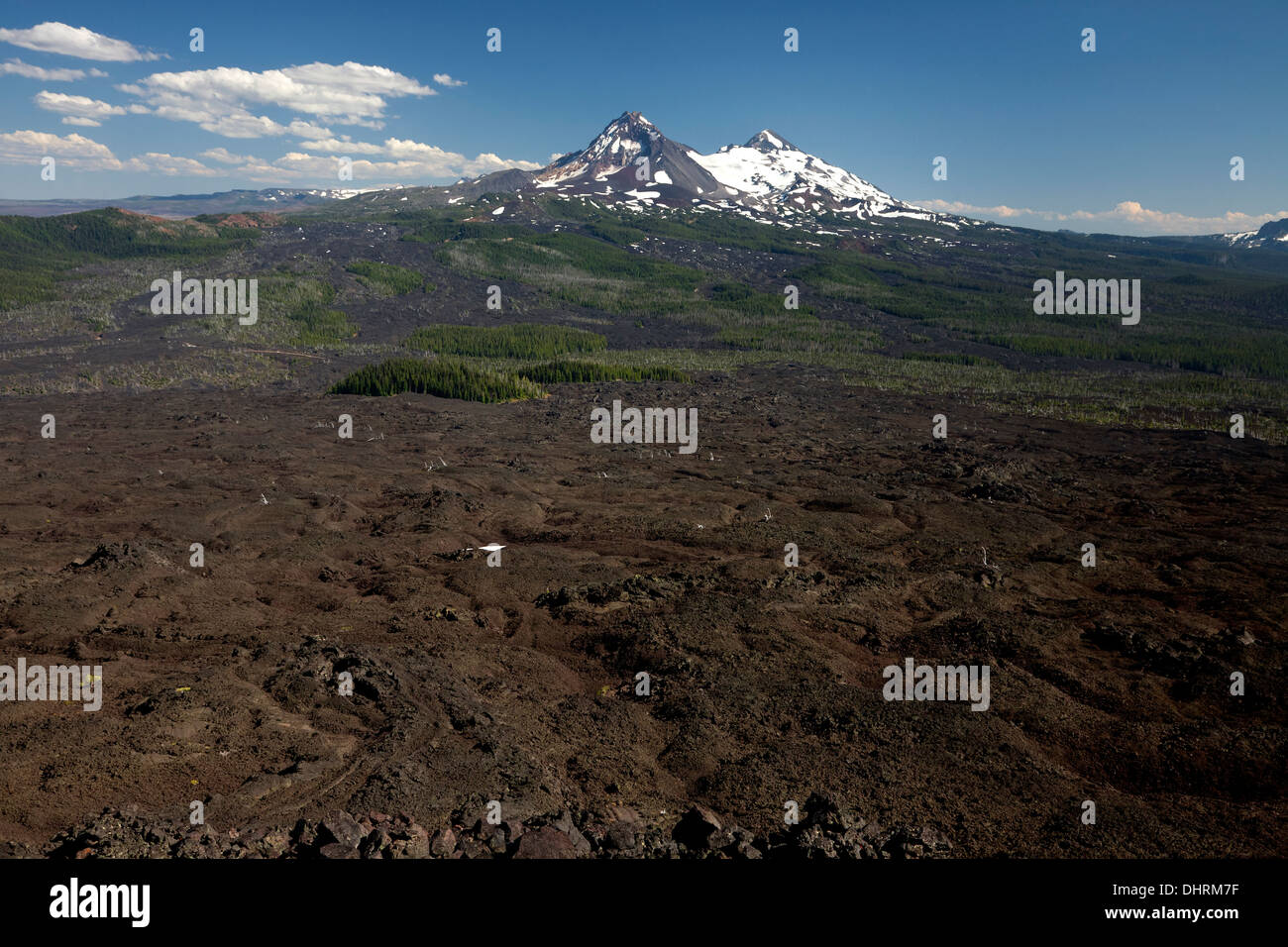 The Lava Flow north of McKenzie Pass and the North and Middle Sisters from the summit of Little Belknap Crater near the PCT. - Stock Image