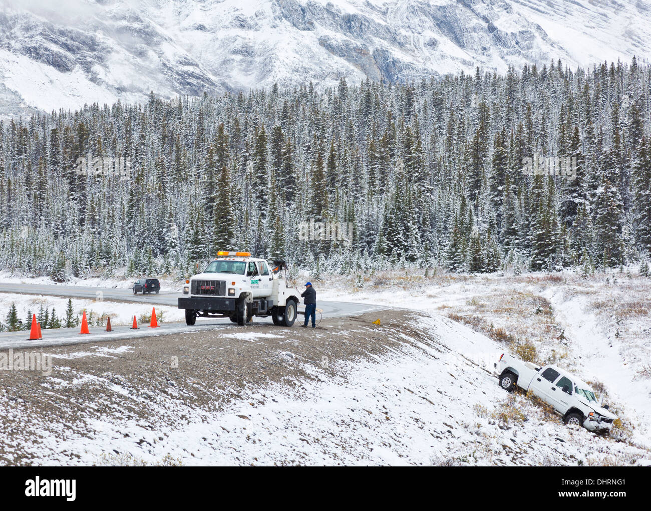 Truck being pulled from ditch after sliding off an icy road Icefields Parkway Banff National Park Alberta Canada - Stock Image