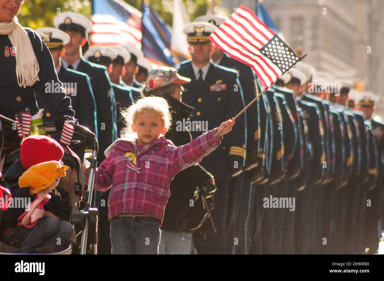 A child of a New York area Coast Guard service member waves the American Flag while marching in New York City's Veterans Day Parade, November 11, 2013. The Parade honors all eras and branches of military service, with special recognition given this year t - Stock Image
