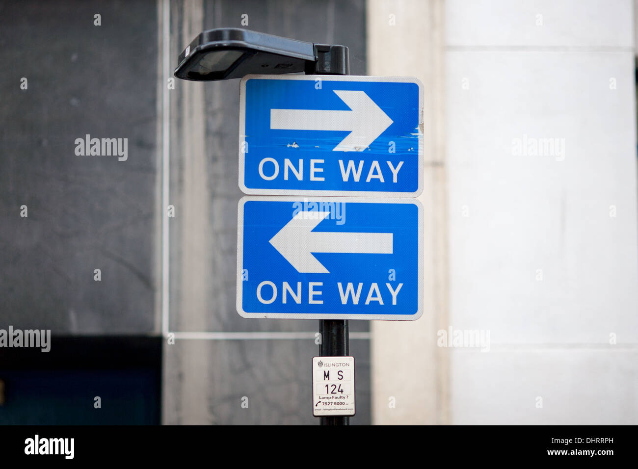 Two one-way traffic signs mounted one above the other but both pointing in opposite directions. London, UK. Stock Photo