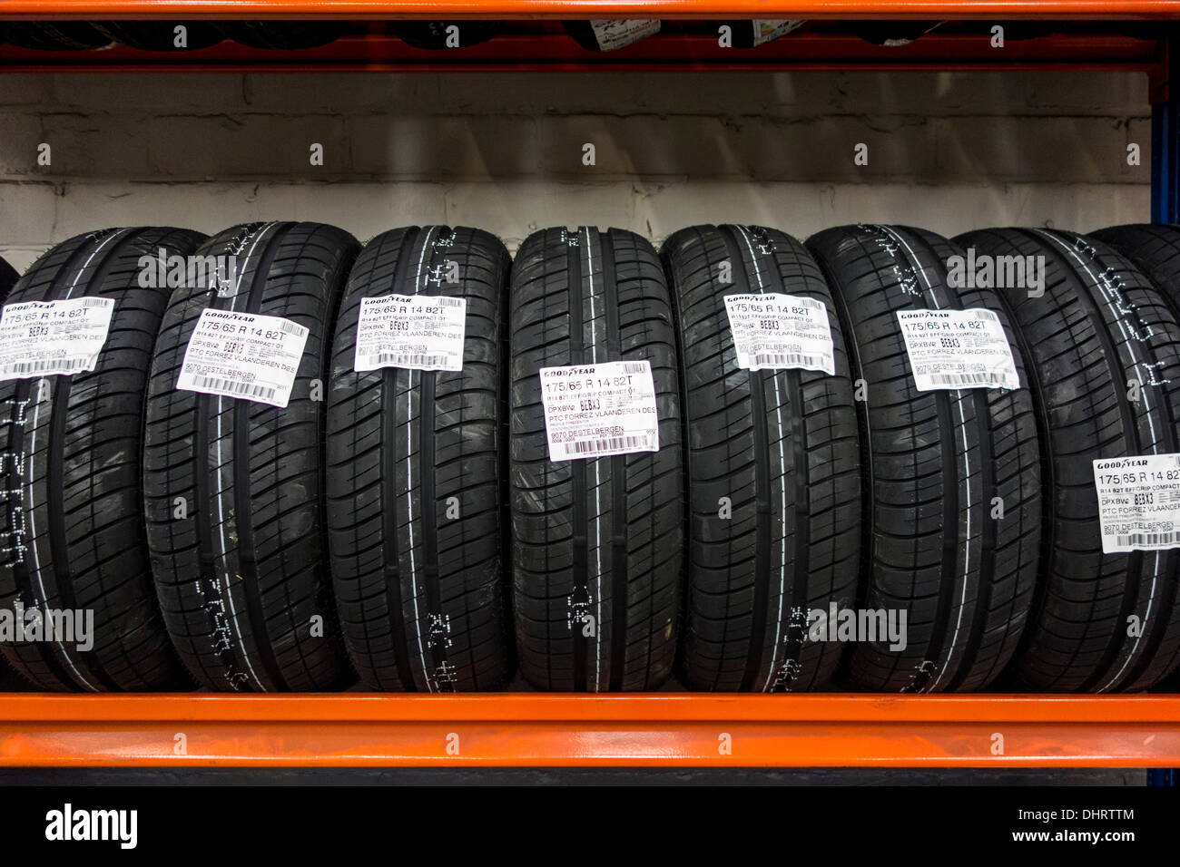 Row of new summer tires for cars stored on shelf in workshop of tire center - Stock Image