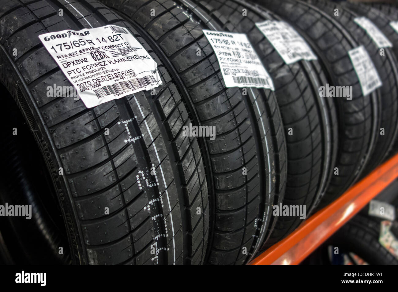 Close up of row of new Goodyear summer tires for cars stored on shelf in workshop of tire center - Stock Image