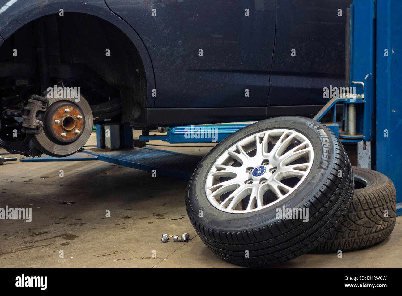 Changing summer tyres and mounting winter tires on wheels of car on ramp in assembly workshop of tire center - Stock Image
