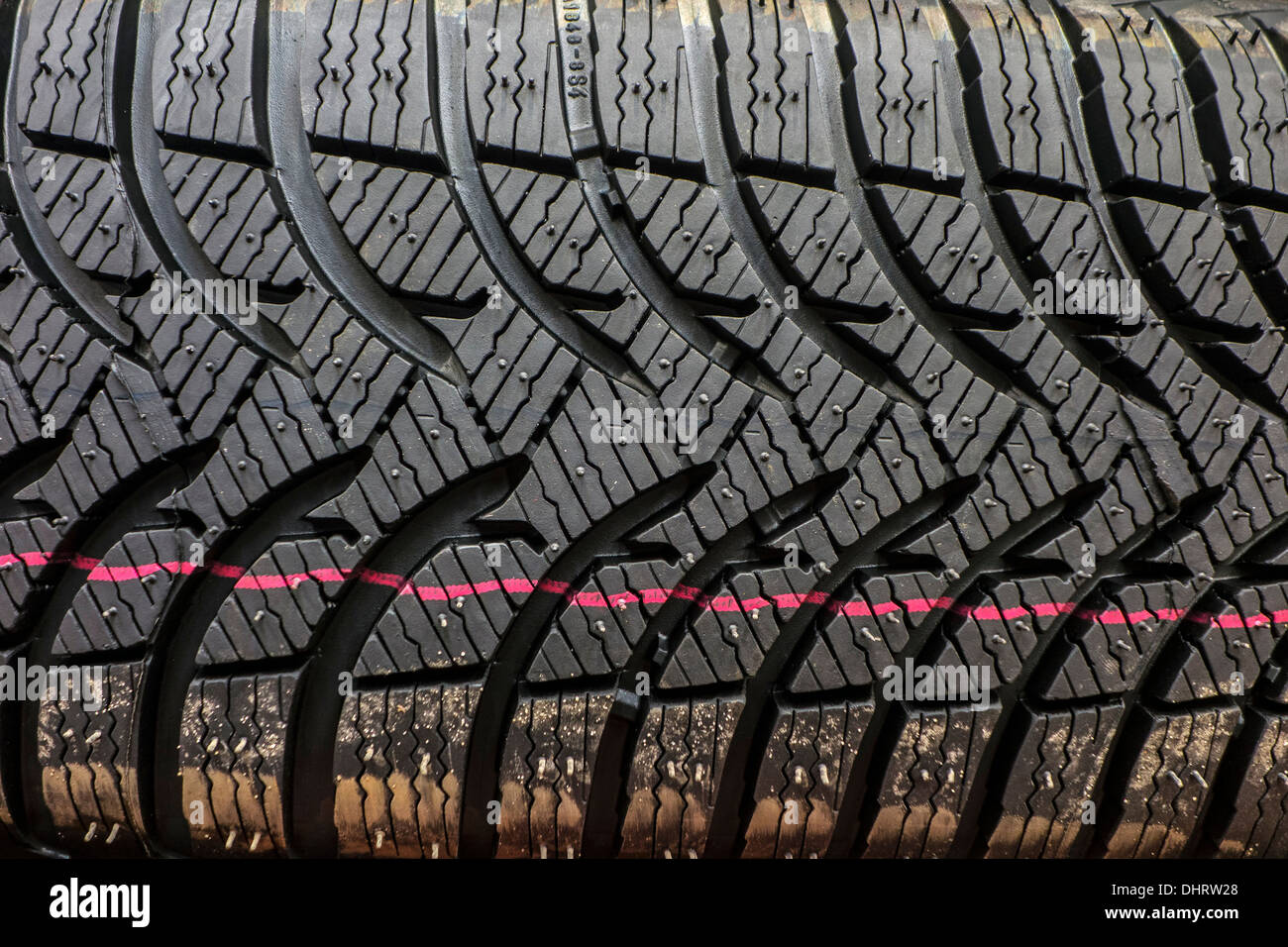 Close up of new winter tire / snow tyre for car showing rubber tread profile with deep grooves and additional sipes - Stock Image