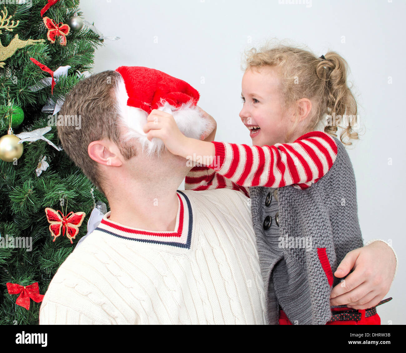 77a502f1 Father and daughter having fun at the christmas. Girl trying to put on  Santa's hat on father.