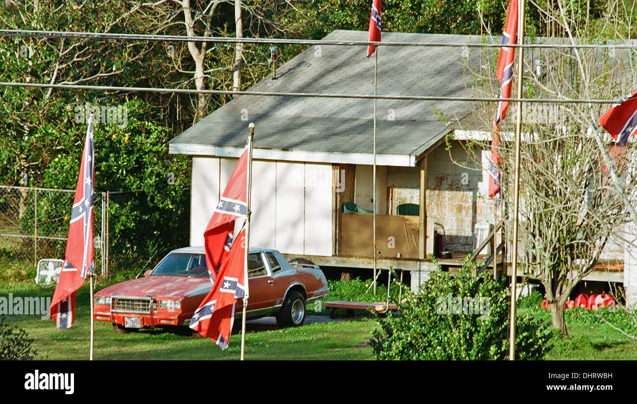 Ramshackle house and car surrounded with confederate flags Stock Photo