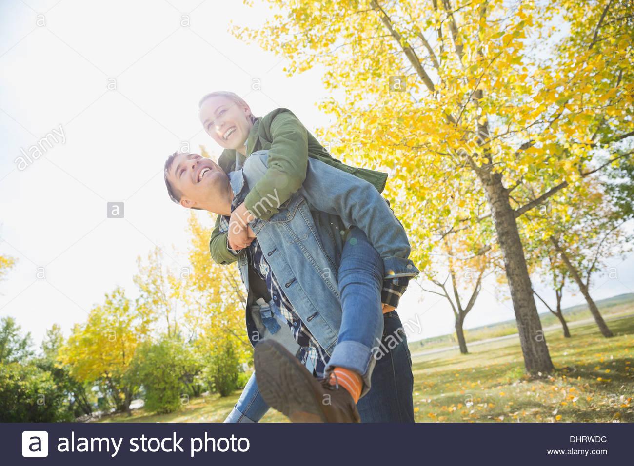 Man piggybacking woman in park - Stock Image